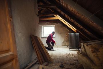 Man repairing old attic in house