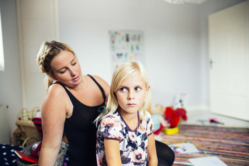 Mother making daughter's hair at home