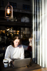 Woman using laptop seen through cafe window