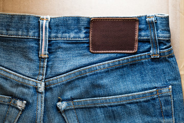 Close-up faded blue jeans back pocket with blank leather tag