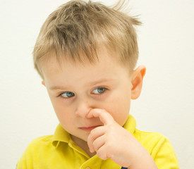 Thoughtful four y.o. boy with wide opened gray eyes in yellow polo shirt is picking his nose on a light gray background