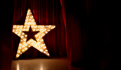 Photo of golden star with light bulbs on red velvet curtain on stage