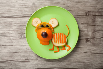 Amusing tiger made of orange on plate and board