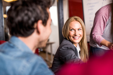 Happy businesswoman discussing with colleague in office