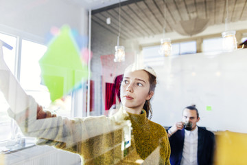 Young business woman writing on glass wall with colleague in background