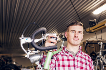 Portrait of confident mechanic carrying bicycle in workshop