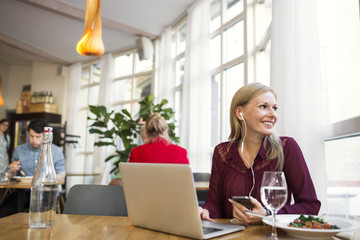 Businesswoman talking through earphones while having lunch at restaurant