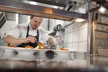 Chef serving food in plate at kitchen counter restaurant