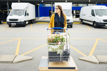 Young woman pushing trolley full of purchases in car park