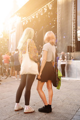 Full length side view of female friends standing at music festival