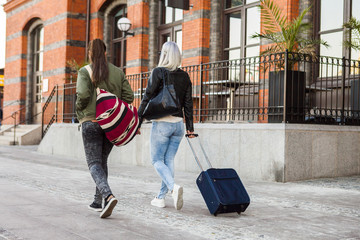 Rear view of female university students with luggage walking on street