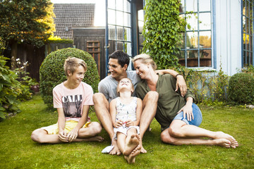 Happy family sitting on lawn in front of house
