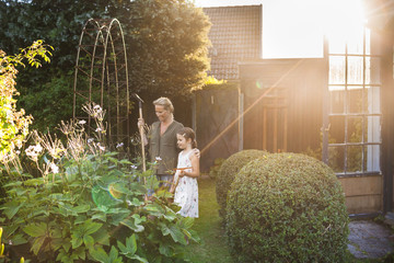 Happy mother and daughter with gardening equipment in backyard