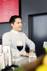Happy young man with glass of red wine on bar counter in restaurant