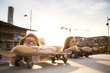 Happy teenage girls relaxing on skateboards at skate park