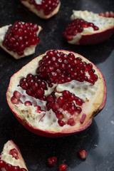 Red juicy pomegranate on dark marble background. Healthy, antioxidant, fresh, gourmet, delicious, organic fruit. Ingredient for grenadine. Close-up and copy space.