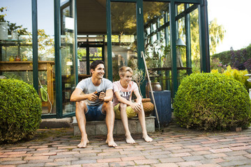 Father and son sitting in front of porch