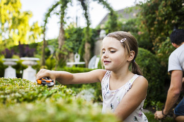 Girl cutting plant with father gardening in background
