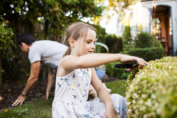 Girl pruning plant with father gardening in background