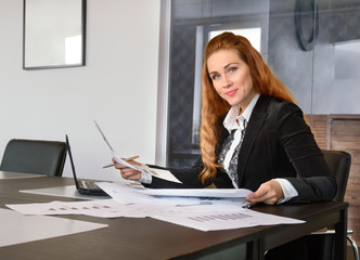 businesswoman working at the office with papers and looking into the frame