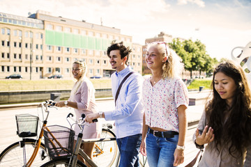 Happy young friends with bicycles walking on street