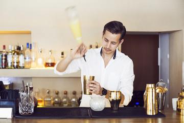 Male bartender making drink at counter in Lebanese restaurant