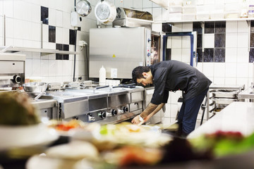 Side view of male chef working in commercial kitchen at Lebanese restaurant