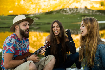 Friends playing music and singing in a lake