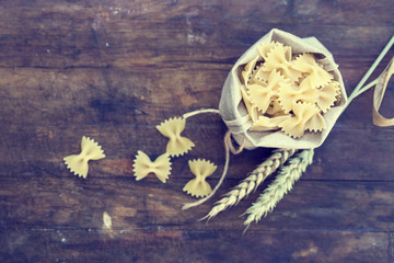 Uncooked Italian pasta farfalle in canvas little bag with wheat ears on dark wooden background. Toned and processing photos with soft selective focus. Shallow depth of field
