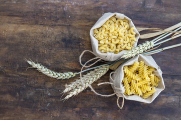 Uncooked Italian pasta Elbow macaroni and Fusilli in canvas little bag with wheat ears on dark wooden background. Shallow depth of field