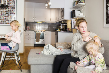 Mother tying girls hair while sitting on couch at home
