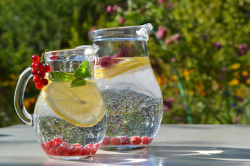 Infused fruit water. Refreshing summer homemade cocktails in glass jugs on outdoor background.