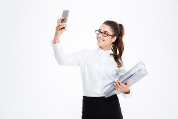 Happy attractive young businesswoman in glasses taking selfie using smartphone
