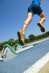 Athlete in gold shoes running a race from the starting blocks on a blue running track