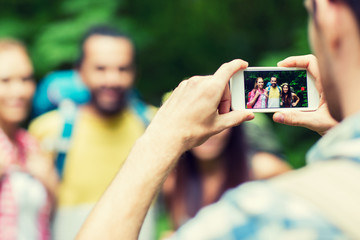 man photographing friends by smartphone