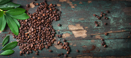 Foto op Aluminium Koffiebonen Roasted coffee beans with green leaves on a vintage background, top view with copy space