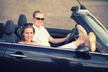 Junge Frau hält lässig ihre Beine aus dem Cabrio - Pärchen im Cabrio in Seitenansicht