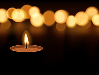 Candle light burning with candle flame bokeh on dark background