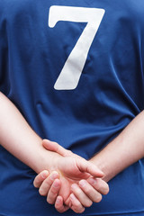 Athlete in uniform stands with hands folded behind his back.