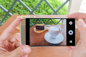 Smartphone take the photo of coffee and cake.