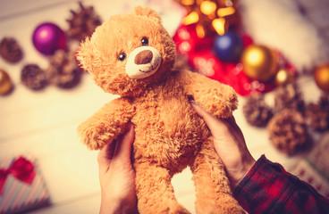 child hands holding a teddy bear