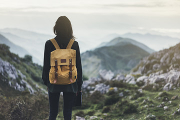 Hipster young girl with backpack enjoying sunset on peak of foggy mountain. Tourist traveler on background landscape mockup. Hiker looking sunlight in trip in spain basque country, mock up for text.