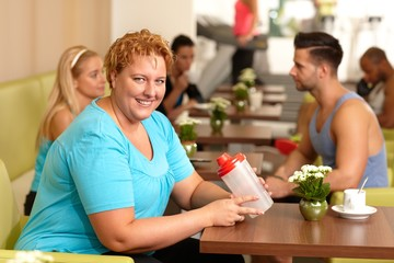 Overweight woman having refreshment in gym