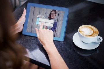 Composite image of woman having coffee and using her tablet