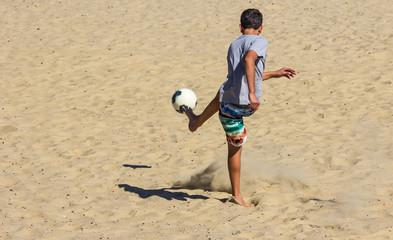 Menino chutando a bola.