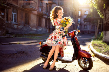 beautiful middle-aged woman with flowers and curly hair sits on a scooter in a dress. In the rays of the sun
