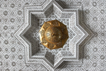 White and golg oriental ornament on the ceiling of a home in Morocco