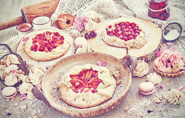 Retro toned rustic set of fruit tarts and meringues, homemade pastry, pastel colors.