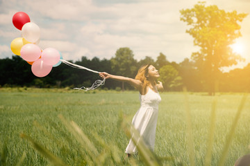 young asian woman on green grassland with colored balloons in th