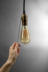 Female hand turning on light bulb on  grey background